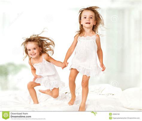giochi sul letto famiglia felice i bambini gemellano le sorelle saltano