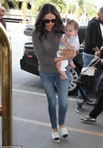 simon cowell and lauren silverman leave baby eric at home lauren silverman cradles son eric at lax one day after tot