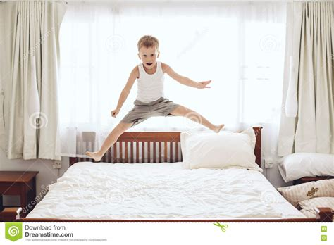 jumping on the bed boy jumping on the bed stock photo image of morning