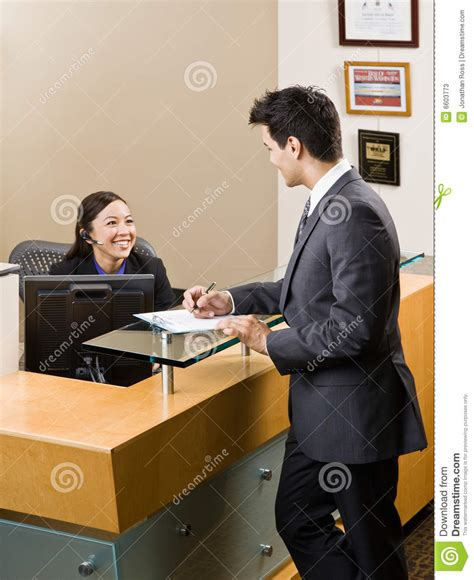 front desk receptionist receptionist greeting man at front desk stock photos