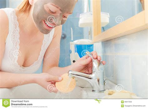 bathroom facial woman removing facial clay mud mask in bathroom stock