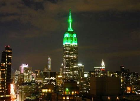 empire state building lit up in green lights to