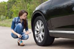 Young woman checking out a flat tyre on her car royalty free stock