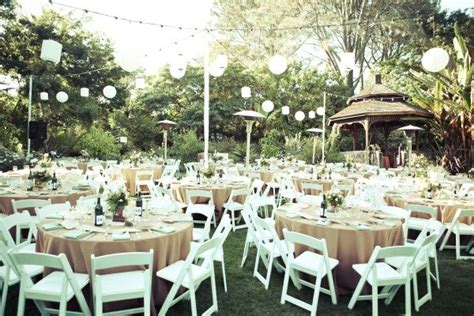 elegant backyard wedding reception lanterns elegant round tables and simple white chairs