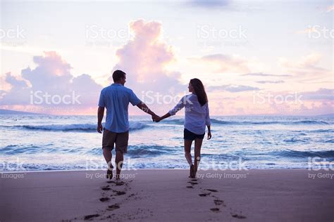 photography lovers lovers walking on the beach at sunset on vacation stock