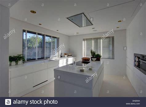 Island unit in modern white kitchen with white Venetian