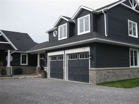 siding house dark blue grey vinyl siding on a house with stone veneer