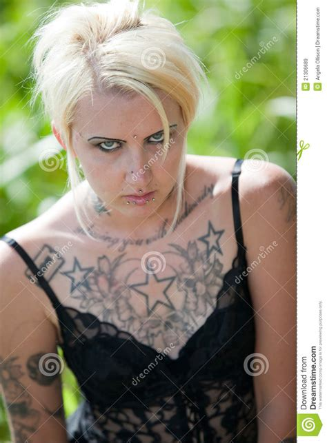 tattooed blonde tattooed standing in field royalty free stock