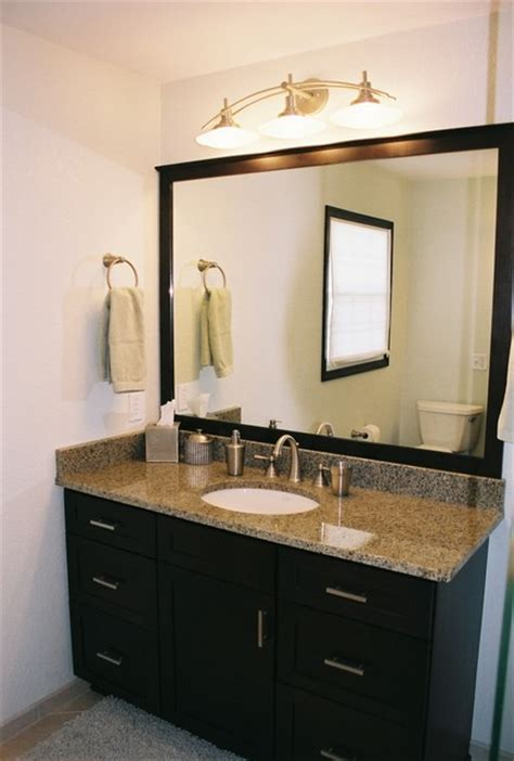 large framed mirror with espresso cabinetry