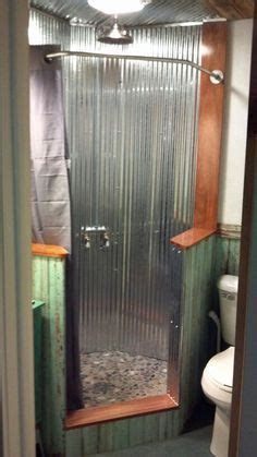 Neo angle shower with corrugated tin walls with river rock