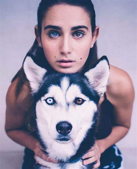 with different colored beautiful heterochromia husky pose with model with