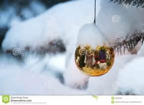 gold christmas tree ornament reflects nativity sce stock