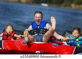 inner tube pulled by boat man being pulled behind boat inner tube stock photos and