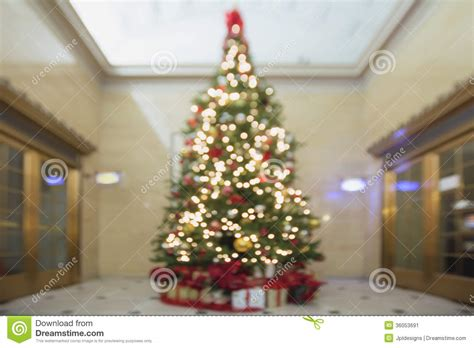 christmas tree with decorations and wrapped gifts bokeh