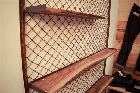 salvaged chain link fence framed walnut shelving
