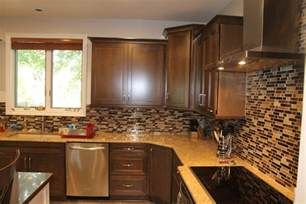 medium maple cabinets with light granite countertops and