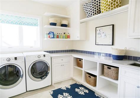 blue laundry white and blue laundry room with cubbies filled with