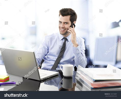 Man Sitting At A Desk Smiling Young Businessman Sitting Behind His Stock Photo