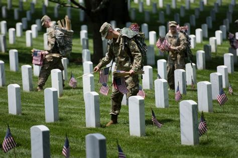 s day in the cemetery soldiers placing 230 000 u s flags at arlington national