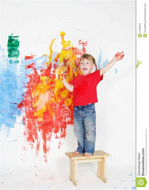 painting for child happy child boy painting wall with colours stock photo