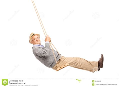 swinging man carefree senior man swinging on a wooden swing stock photo