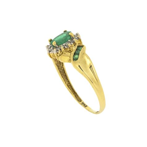 oval emerald and cluster ring in 18ct gold