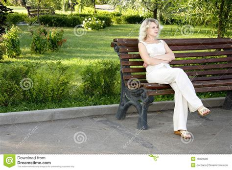 sad bench beautiful sad young woman sitting on the bench stock photo