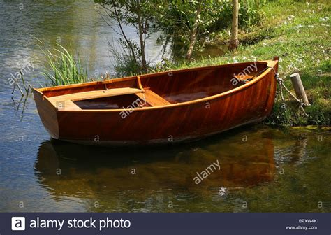 a small wooden row boat is tied to shore stock photo - Row Boat En Francais