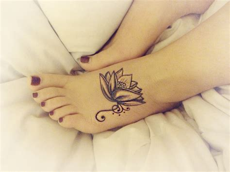 small flower foot tattoo lotus flower on foot with swirls black grey and