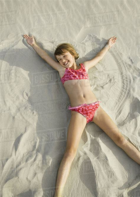teens spreding girl making angel in sand on beach high angle view