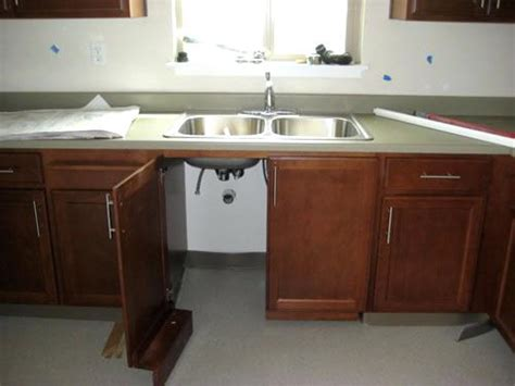 View of kitchen cabinets showing door under sink open for ada cabinet requirements compliant