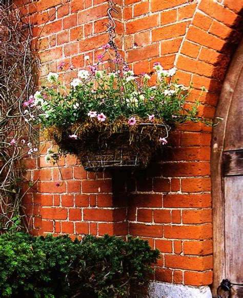 a brick wall is adorned with a hanging garden planter