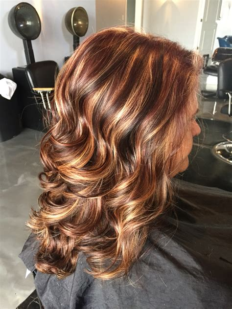 medium length hair style low lights maghagony all over base with thick chunky honey highlights
