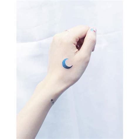 blue spectrum moon tattoo on the left hand tattoo artist