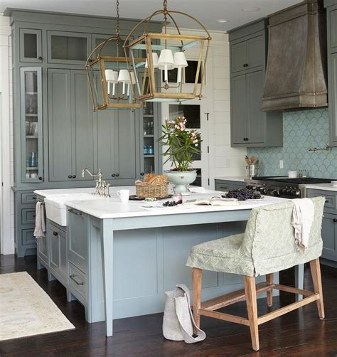 green kitchen cabinets with blue fan tile backsplash