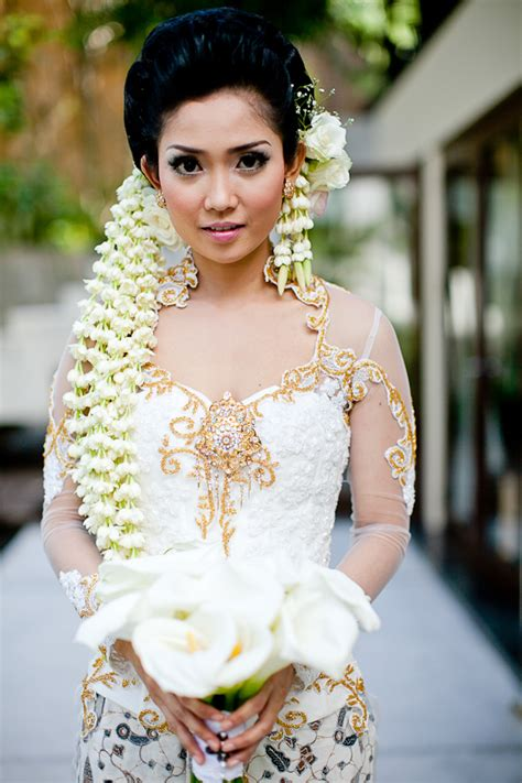 indonesian wedding bride in indonesian wedding garb with lily bouquet