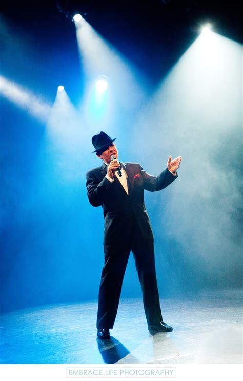 frank sinatra impersonator singing  stage lighting