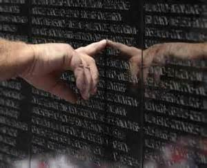 Visitor to the vietnam veteran s memorial touches the name of a