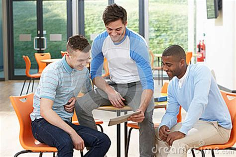 male architect with digital tablet studying plans in three male students looking at digital tablet in classroom