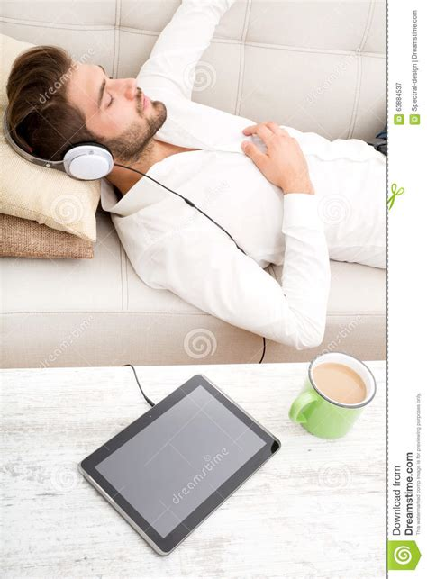 music on the couch young man listening to music stock photo image 63884537