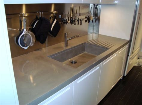 Oversized concrete countertops including an integrally cast kitchen farm sink with drainage