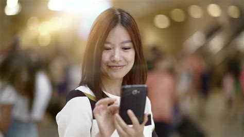 who is the asian girl in the mobile strike commercial asian woman using app on smartphone smiling and texting on