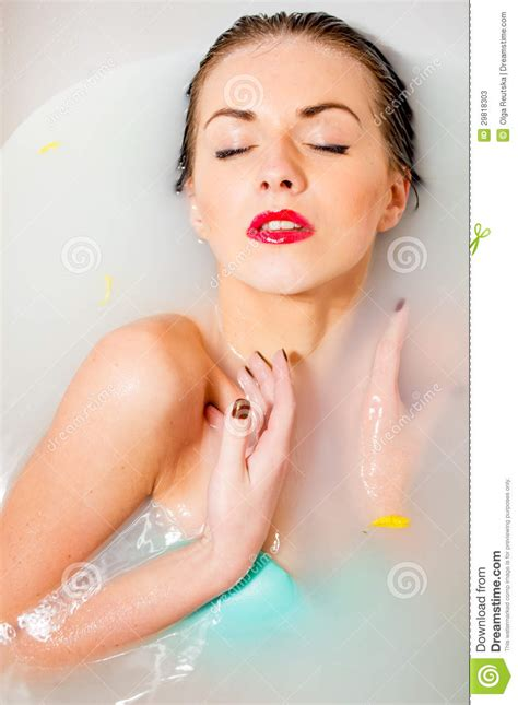 sexy bathtub woman relaxing in milk bath with flowers stock image