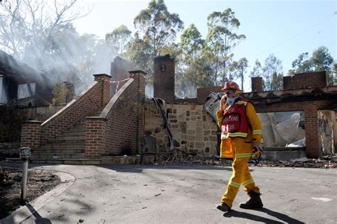 a member of the cfa walks past a destroyed home in