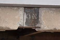 cracked concrete exposes the steel beam along the