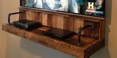 diy pallet wood floating tv shelf idea that hides your