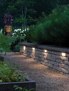 this retaining wall is accented with hinkley s hardscape lighting helping illuminate the path