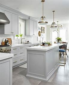 light gray cabinets with white glazed subway tiles transitional kitchen
