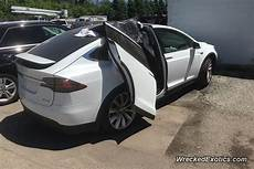 tesla model y doors tesla model x exits garage with falcon wing door open