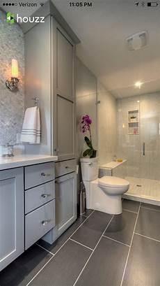 bathroom dark grey tile flooring light grey cabinets white countertop white light grey tile